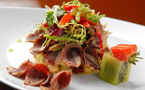 Салат с копченой колбасой на тарелке