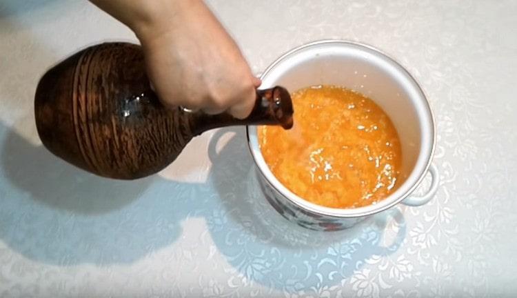 Выкладываем пюре из мандаринов в кастрюлю и заливаем водой.