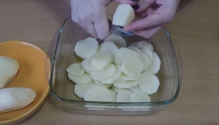Нарезаем прямо в форму картофель кружочками.
