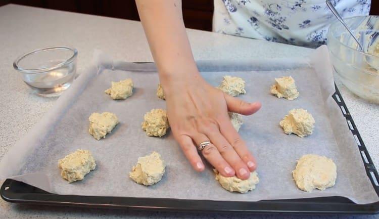 Разравниваем печенье смоченными в воде пальцами.