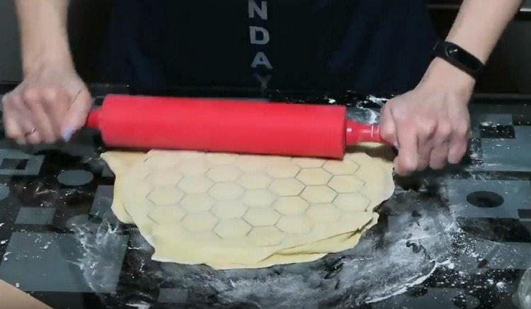 накрываем пельменницу с заготовками еще одним раскатанным пластом тест и при помощи скалки выдавливаем пельмени.