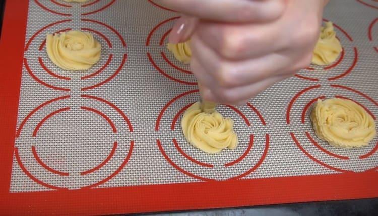 При помощи кондитерского мешка отсаживаем на силиконовый коврик или пергамент печенья.