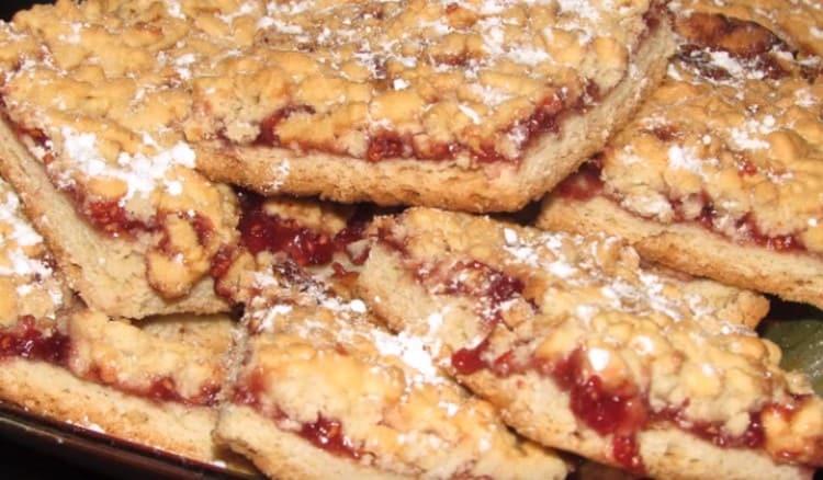 При подаче песочное печенье с вареньем и крошкой можно посыпать дополнительно сахарной пудрой.