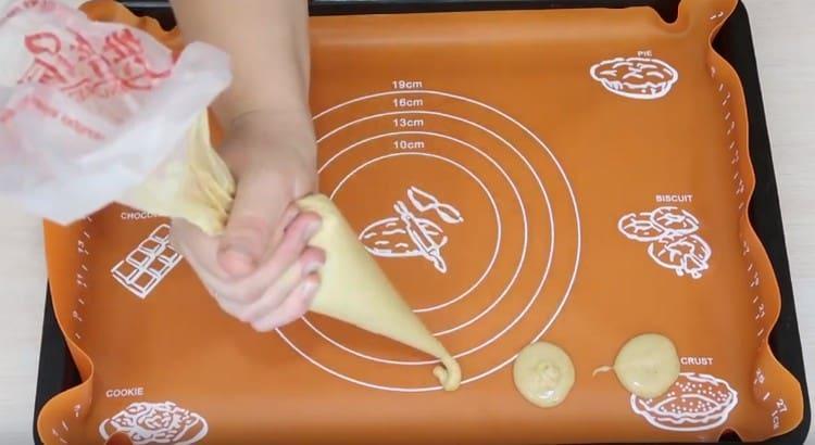 При помощи кондитерского мешка отсаживаем на коврик печенье.