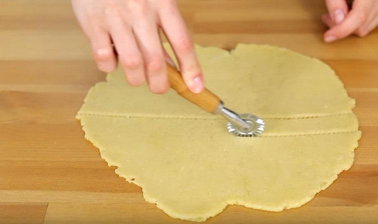 Фигурным или простым ножом нарезаем тесто на полоски.