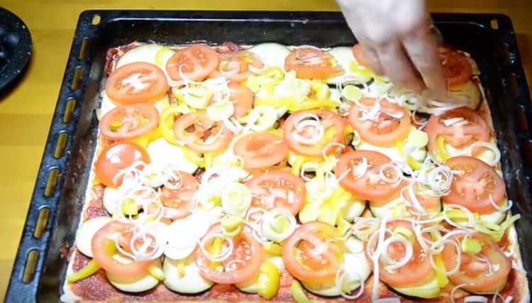 Поверх перца делаем слой из помидоров и посыпаем их луком пореем.
