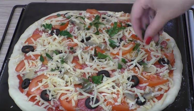 Посыпаем пиццу сыром.