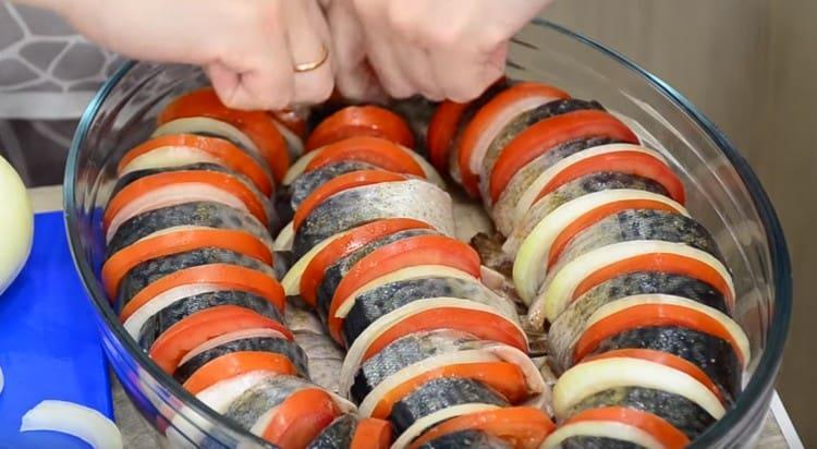 В смазанную растительным маслом форму выкладываем кусочки рыбы, чередуя их с ломтиками лука и помидора.