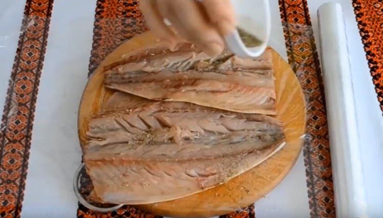 Раскладываем рыбное филе на пищевой пленке, посыпаем солью и специями.