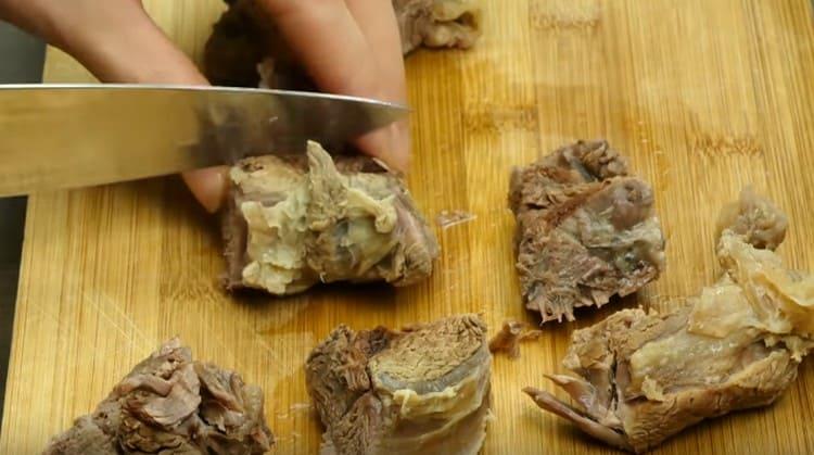 Мясо студим и нарезаем на небольшие кусочки.