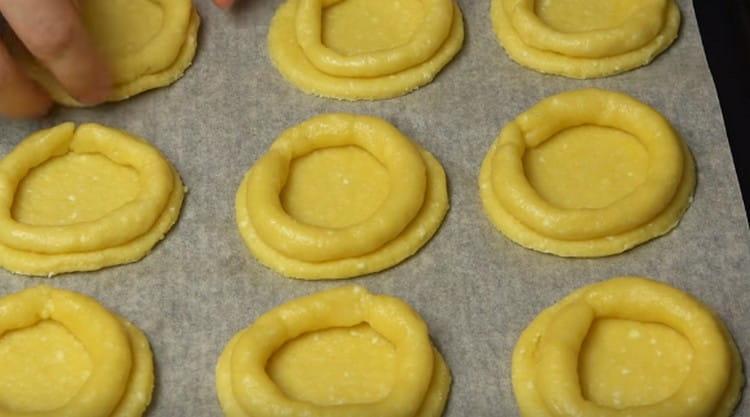 Из части теста делаем жгутики и формируем из них бортики на ранее вырезанных кружочках.