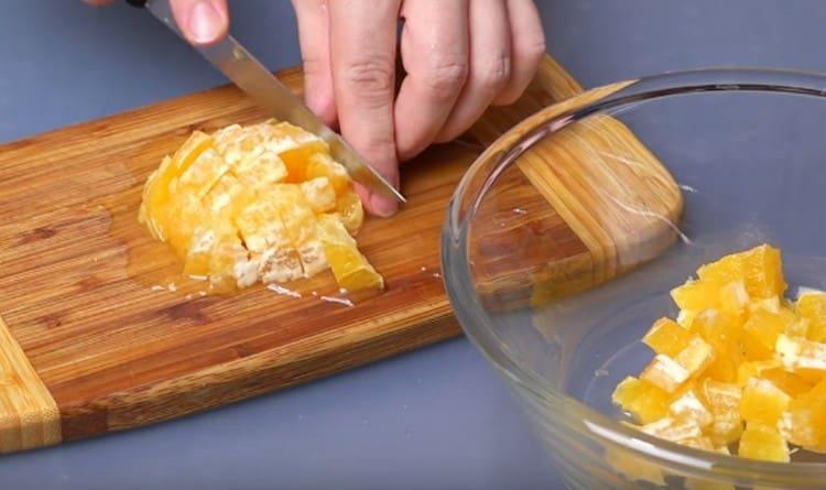 Нарезаем кубиком апельсины.