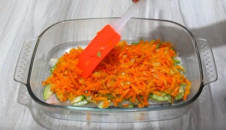 Поверх рыбного филе выкладываем кабачковый слой, а на него уже морковь с луком.