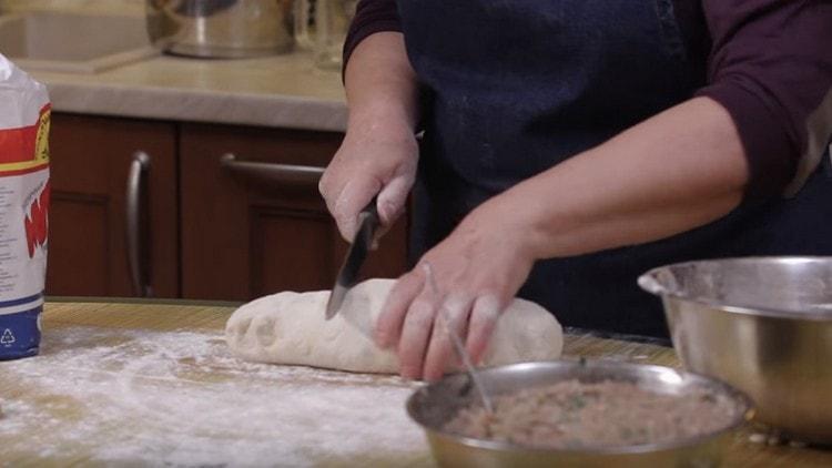 Обминаем тесто и отрезаем от него небольшой кусок.