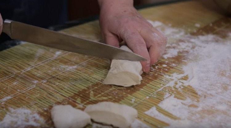 Скатываем тесто в жгут и нарезаем на порционные кусочки.