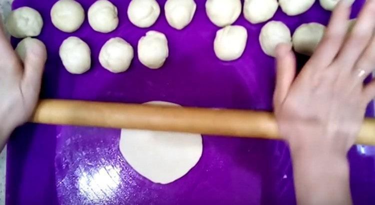 Тесто делим на кусочки и раскатываем их скалкой.