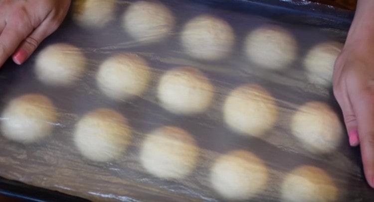 Накрываем булочки на противне пленкой и даем им еще немного подойти.