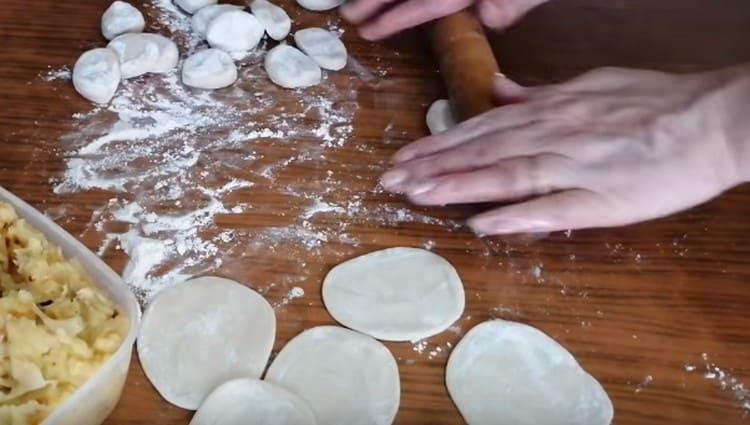 Нарезаем колбаску на кусочки, каждый из них обваливаем в муке и раскатываем.