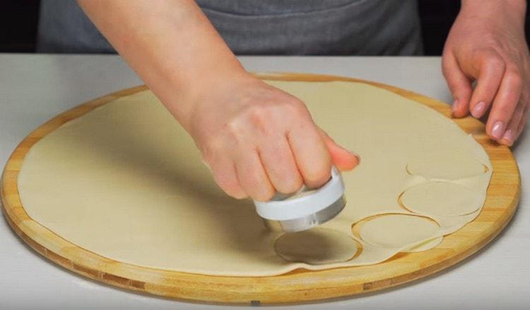 Раскатываем тесто и вырезаем из него кружочки для вареников.