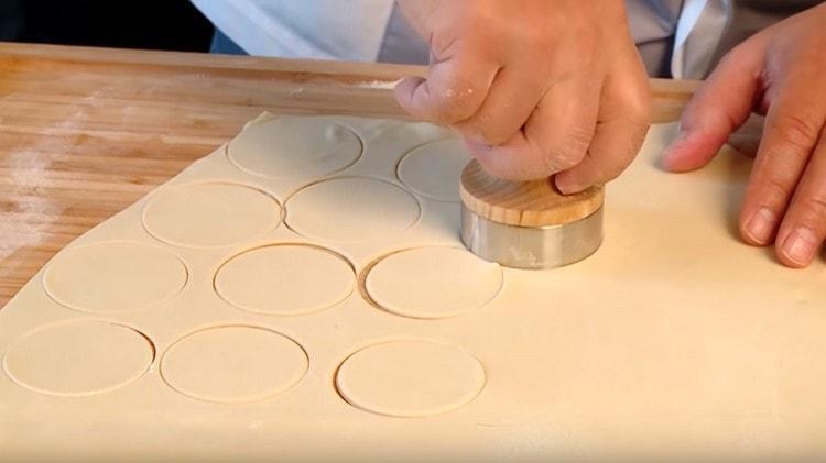 При помощи формы или стакана вырезаем из теста кружочки.