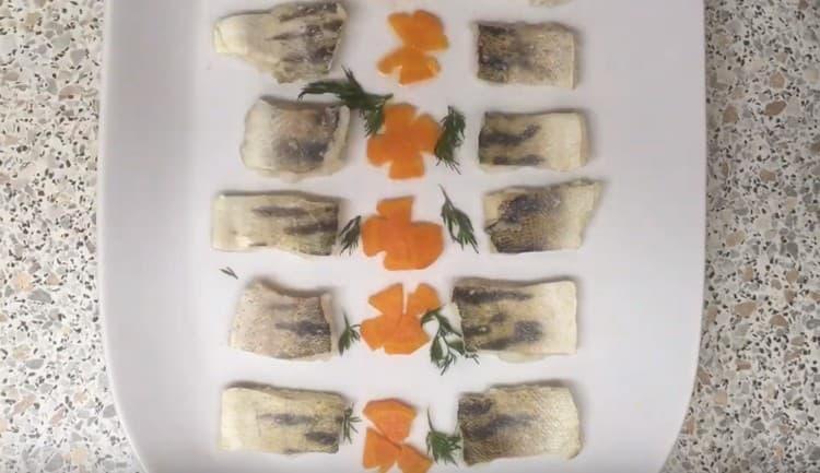 Между кусочками рыбы красиво раскладываем украшения из моркови и зелени.