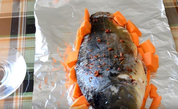 Обкладываем рыбу брусочками моркови.