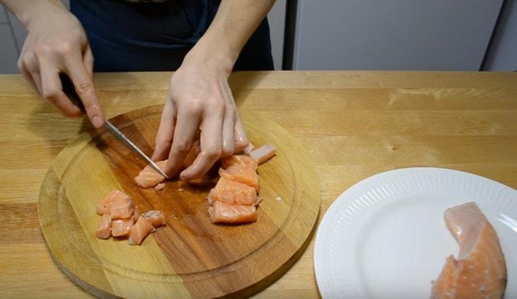 Для начинки нарезаем лосося на кусочки.