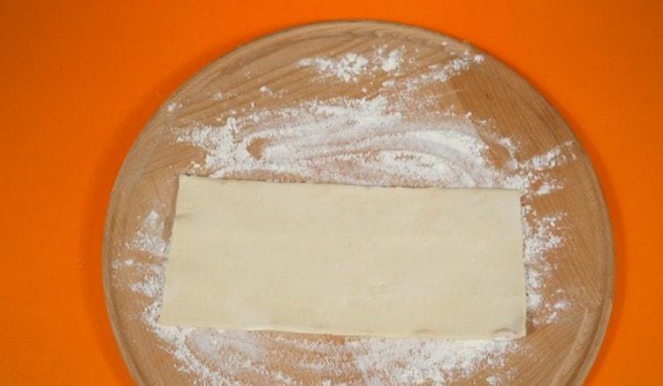 Размороженное слоеное тесто выложите на присыпанную мукой поверхность.