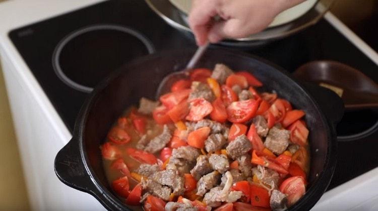 Нарезаем помидоры на кусочки и добавляем на сковороду.