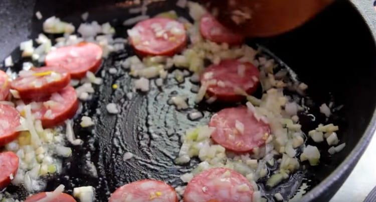 Выкладываем обжариваться лук, чеснок и колбасу.