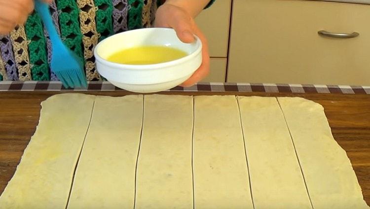 Смазываем каждую полоску теста растопленным сливочным маслом.