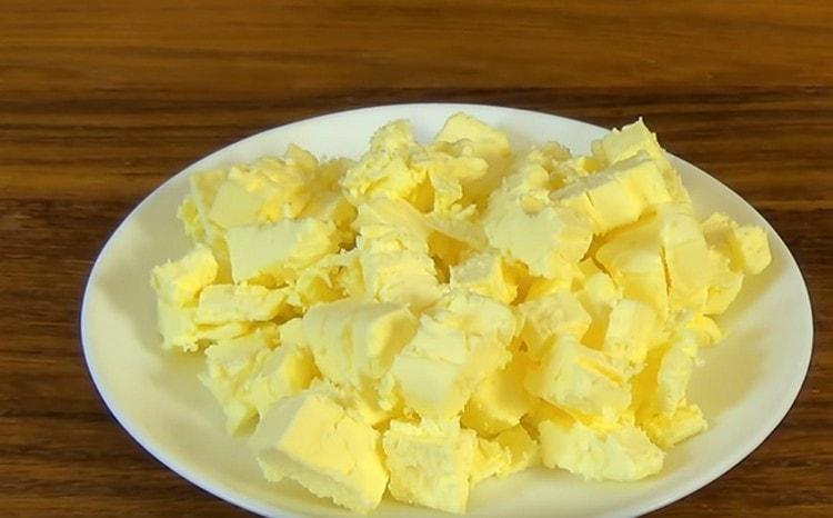 Нарезаем холодное сливочное масло на кусочки.