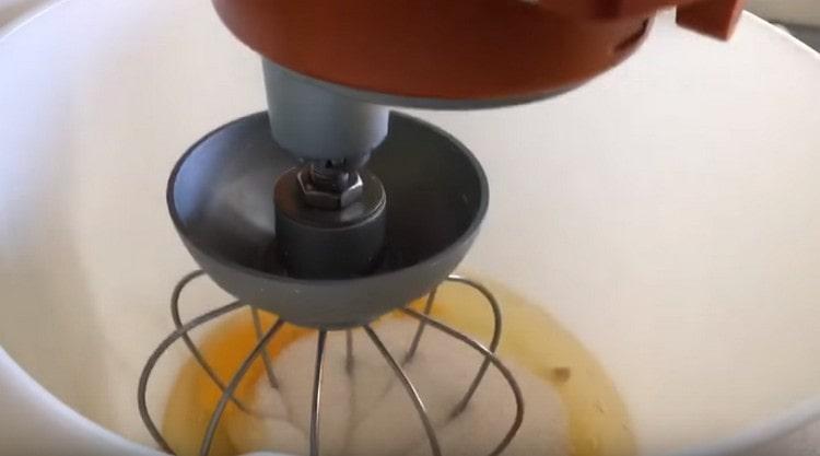 Добавляем к яйцам сахар и взбиваем миксером.