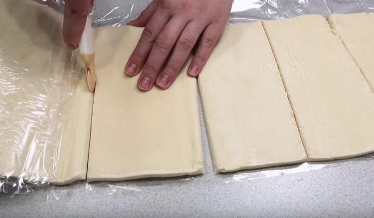 Слоеное тесто разделяем на части.
