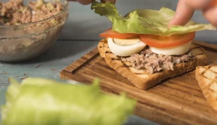 Поверх тунца выкладываем кусочки яйца, кружочки помидора и листик салата.