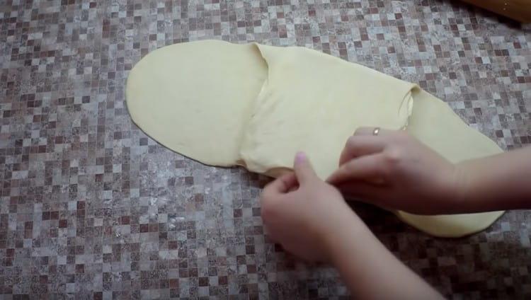 На центр полученной лепешки кладем размягченное сливочное масло и накрываем его лепестками теста.