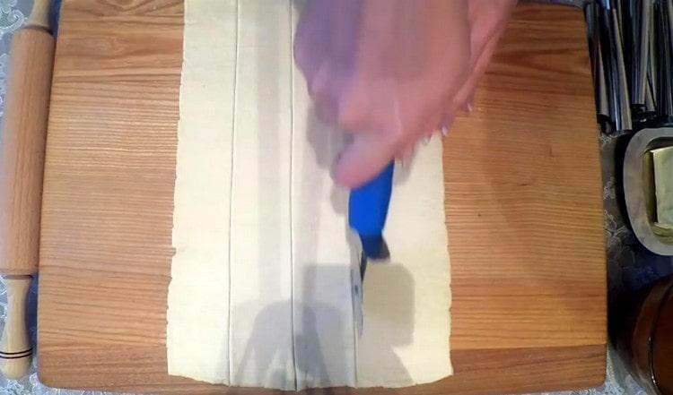 Слоеное тесто раскатываем в прямоугольник и нарезаем его на полоски.