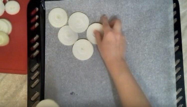 Выкладываем на пергамент по диагонали луковые кольца.