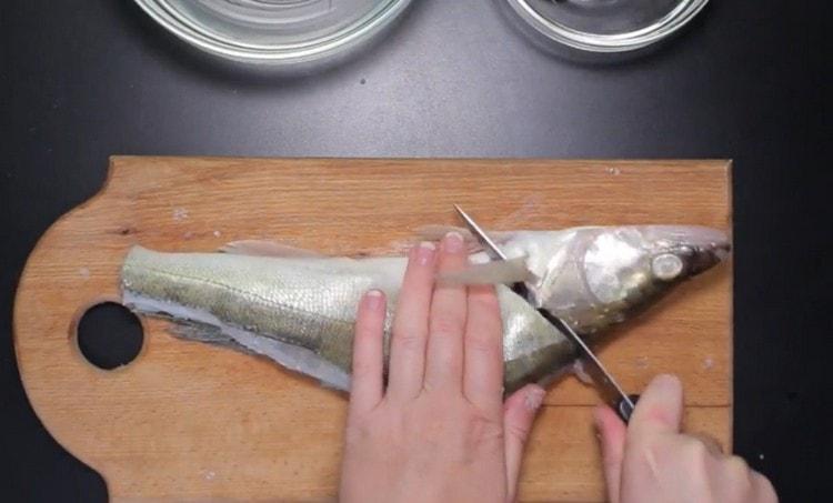 Не дорезая до конца, отделяем голову рыбы от туловища.