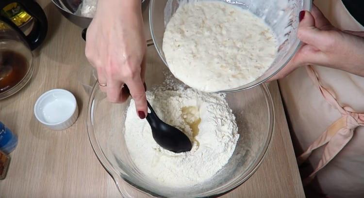 Понемногу добавляем опару и перемешиваем тесто.