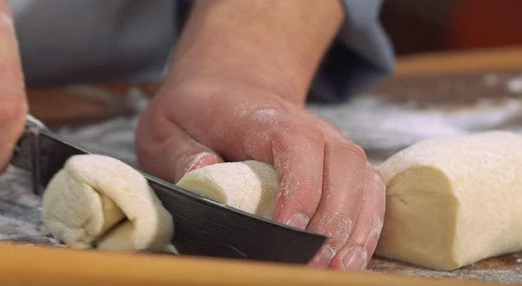 Каждый кусок теста скатываем в колбаску и нарезаем ее на порционные заготовки.