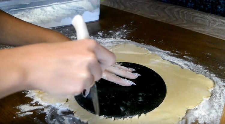 Используя в качестве шаблона дно формы для выпечки, вырезаем из теста круг.