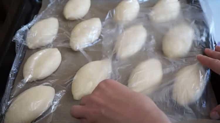 Для приготовления пирожков с луком и яйцом положите тесто на противень