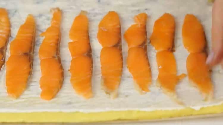 Для приготовления рулета с красной рыбой, выложите нарезаную рыбу на тесто