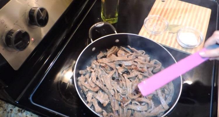 Выкладываем мясо и обжариваем на большом огне до румяности.
