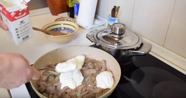 Добавляем сметану и размазываем ее сверху по мясу.