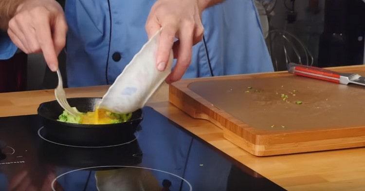 кусочки брокколи выкладываем на сковороду, заливаем яйцом и готовим под крышкой.