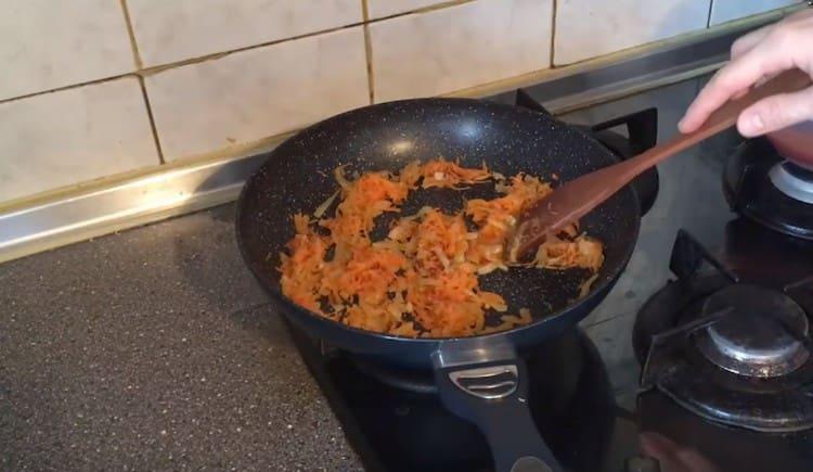 Добавляем к луку натертую на терке морковку.