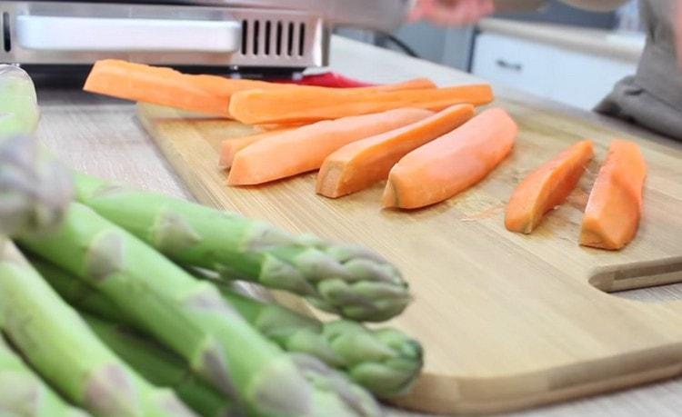 Чистим и нарезаем брусочками морковь.