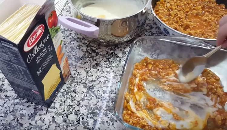 На дно формы выкладываем немного соуса болоньезе и бешамель, перемешиваем.